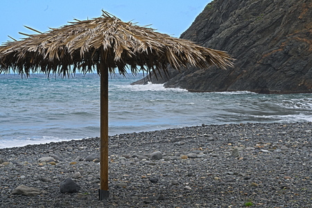 palm  branch parasol at a lonely stone beach, the ocean and a blue sky in the background 스톡 콘텐츠