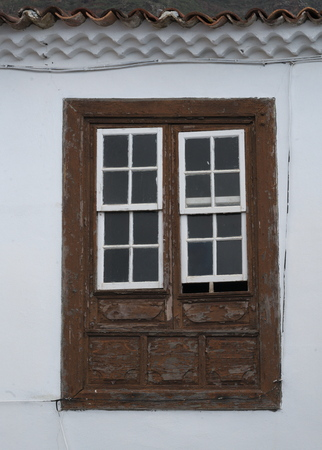 Old wooden strutted brown window of a white house Banco de Imagens