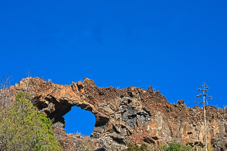 Perforated rock like a bridge in front of a blue sky