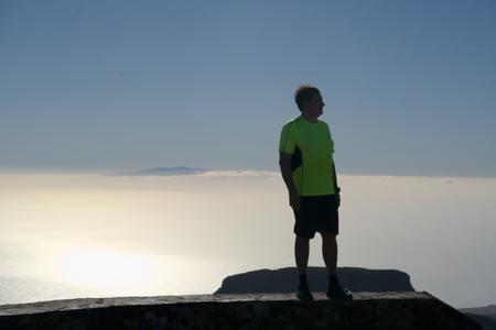Man over the sunny clouds Фото со стока