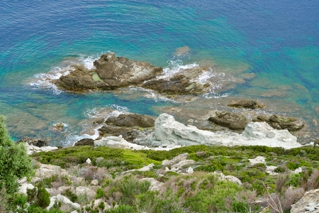 green riff in front of a green-turquois sea with rocks in the water 版權商用圖片