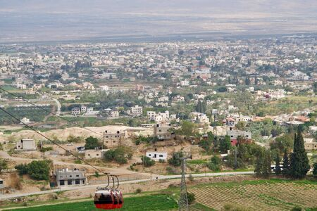 three red cable cars in front of the city of Jericho Stock Photo