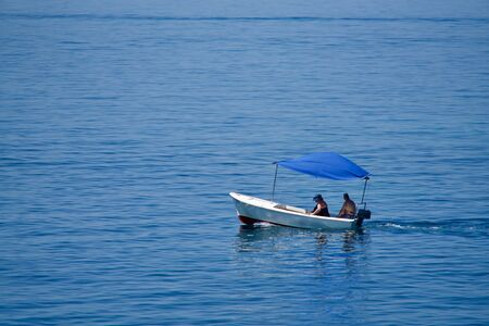 Couple in a little boat with a blue top on the sea