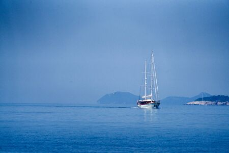 White sailing boat in front of the croatian coastline Stok Fotoğraf - 129983301