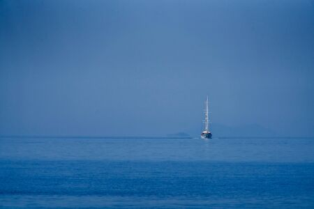 White sailing boat approaching on the blue sea Stok Fotoğraf