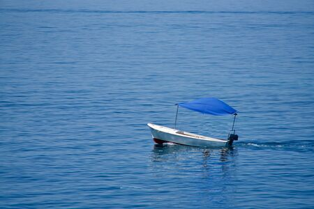 Empty little boat with a blue top on the sea