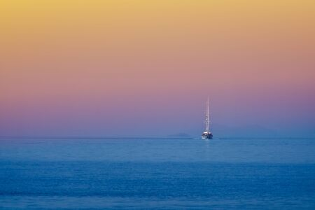 White sailing boat approching on the blue sea