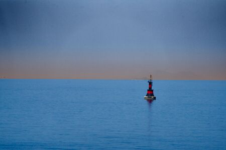 red-black buoy in the blue sea