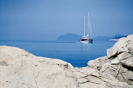 White cliff, sailing boat on the ocean behind
