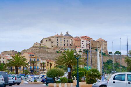 Old city of Calvi under a blue, light cloudy sky