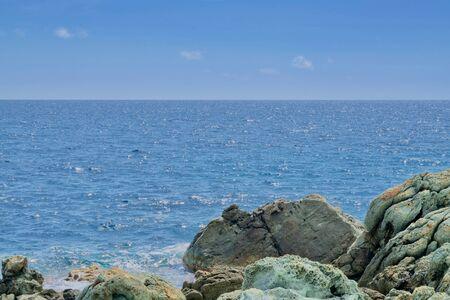 Green-beige rocks in front of the ocean under a blue sky