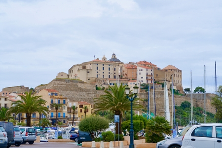 Old town of Calvi under a blue, light cloudy sky