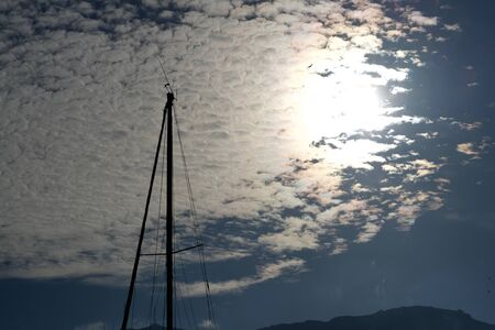 Mast of a sailing boat in the twilight under a cloudscape