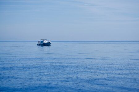 Fisherman on a rubber boat on the blue sea and under a blue sky Stok Fotoğraf