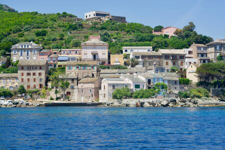 Corsican homes on a greened cliff at the blue sea