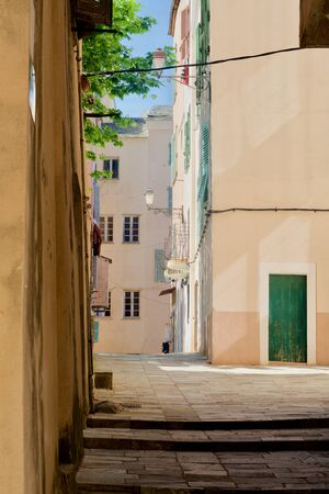 Empty alleys between yellow homes with green shutters Reklamní fotografie