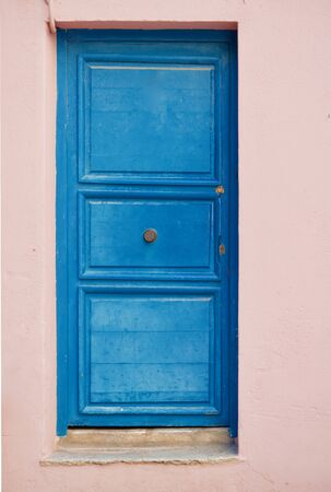 Close-up of an old blue door or a rose colored home