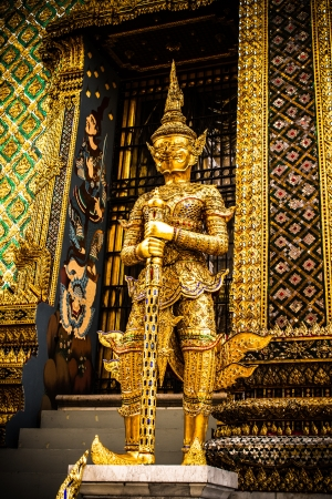 The beautiful of golden giant  smile statue of the Emerald Buddha temple(Wat phra kaew) and Royal Grand Palace ,Bangkok,Thailand. Stock Photo