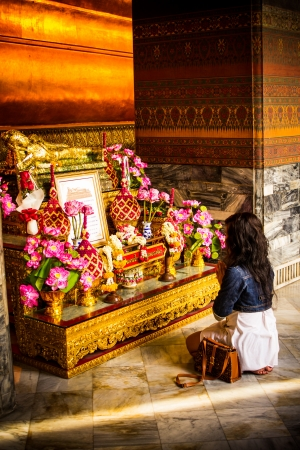 Woman that pay homage to Buddha image in  Wat Pho, Bangkok, Thailand