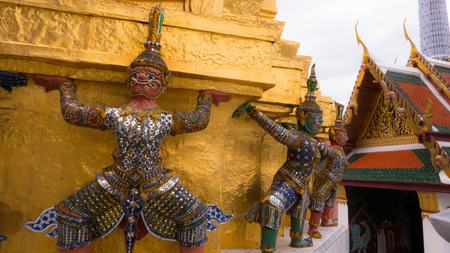 kaew: The beautiful of giants  statue under golden pagoda of the Emerald Buddha temple(Wat phra kaew) and Royal Grand Palace ,Bangkok,Thailand. Stock Photo