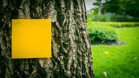 graden: Orange sticky note on tree with graden background. Selective focus.