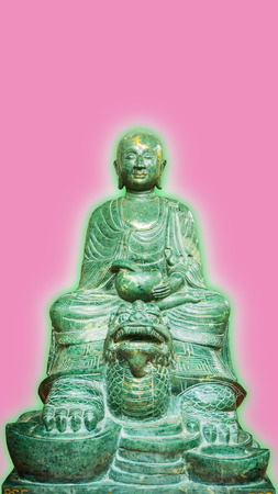 aura: Old Buddha stone green (Lucky stone)Statue Isolated with green aura on a Pink Background.