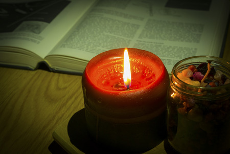 holiday prayer book: In dark . Vintage style image of candle light with Book on the background. Stock Photo