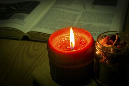 santa cena: En la oscuridad . Imagen del estilo de la vendimia de la luz de las velas con el libro en el fondo.
