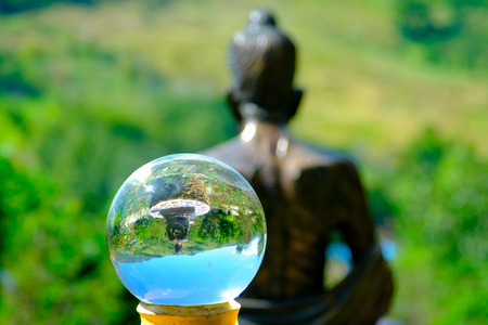 Glass transparent ball on back view of Buddha Statue with mountain at Wat Phasornkaew in Thailand. Photo taken on: 29 November , 2016