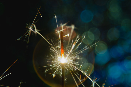 Christmas and New Year party sparkler with abstract circular bokeh background Christmas lights. Stock Photo