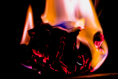 Beautiful concept flames. Fire on burns paper with black background. Soft Focus