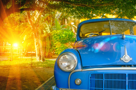 Bangkok, Thailand - December 11, 2016 : Detail of front view blue retro car with lighting flare effect. Vintage style