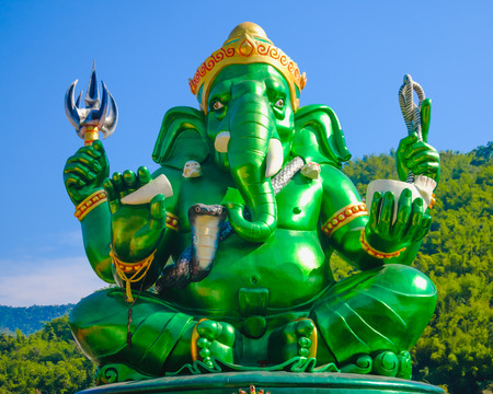Beautiful green big Ganesha Hindu God statue with blue sky and mountain background in public temple in Thailand , Ganesha God is elephant God in Hindu religion.