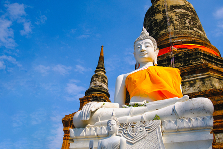 White old buddha statue with blue sky background at Wat Yai Chai Mongkhon Old Temple in Ayutthaya Historical Park Thailand.