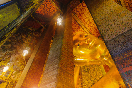 wat pho: Selective face focus of Reclining golden Buddha statue with thai art architecture in church Wat Pho (Temple of the Reclining Buddha) in Bangkok,Thailand. Editorial