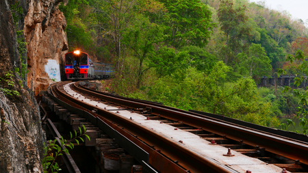 Trains running on railways track crossing kwai river in kanchanaburi thailand this railways important destination of world war II history builted by soldier prisoners Stock Photo