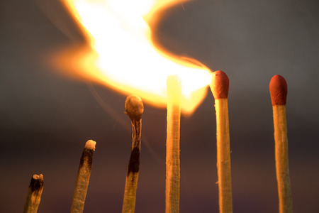 Row of matches starts buring, Metaphor for ideas and inspiration Stock Photo