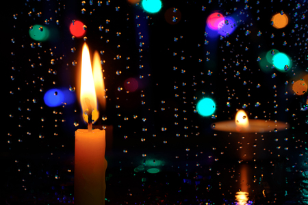 Candle stands in front of a window with blur rain drops and light bokeh background in night Stock Photo