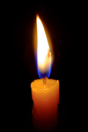 Light candle burning brightly with night background.