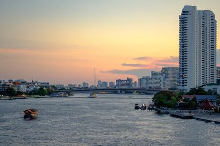 Chao Praya River in Bangkok, buildings and Small Thai boat cruise at sunset Stock Photo