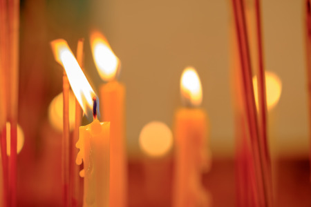 coherence: Many candle flames glowing in the night, create a spiritual atmosphere  at thailand temple. Stock Photo
