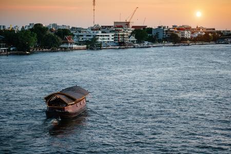 Chao Praya River in Bangkok, buildings and Small Thai boat cruise at sunset Editorial