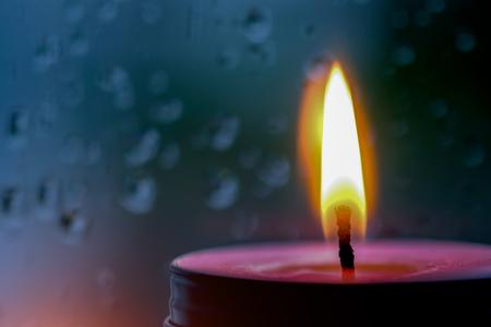 Image Vintage de la lumière de la bougie rose à l'avant à la fenêtre avec des gouttes de pluie floue et fond de nature faible lumière. Banque d'images - 79348143