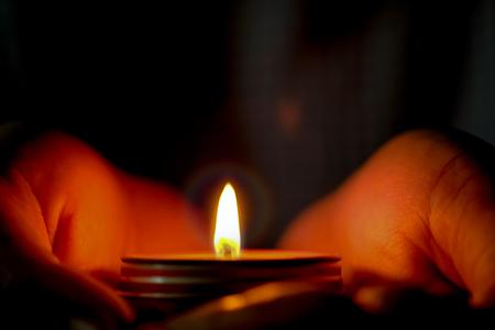 Concetto di preghiera e speranza di luce di candela nelle mani.