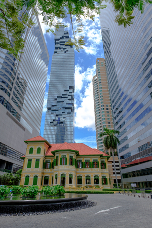 BANGKOK THAILAND - JUNE 8, 2017 : View of Cafe in W Bangkok Hotel by street (Old Russian Embassy). Old Yellow vintage style Building between two skyscrapers on North Sathorn Road. Editorial