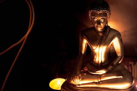 Selective focus of buddha statue with blurred burning candle light in soft night light with line light . Concept of peace, meditation, hope and relaxation.