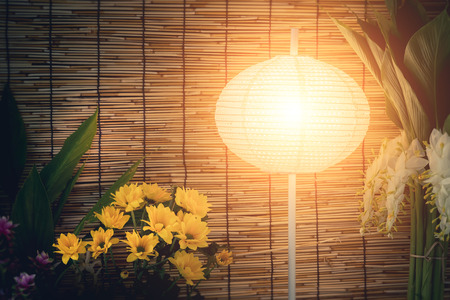 Vintage image on classic lantern and flowers with Bamboo weave texture pattern background. Stock Photo
