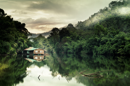 Mountain forest with fog and houseboat on kwai river landscape on rain in kanchanaburi, Thailand. Natural concept.