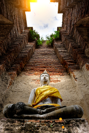 Ancient Buddha and old brick wall on ancient monuments that are over 200 years old. Wat Nakhon Luang Tample,Prasat Nakhon Luang public domain or treasure of Buddhism in  Ayutthaya, Thailand.