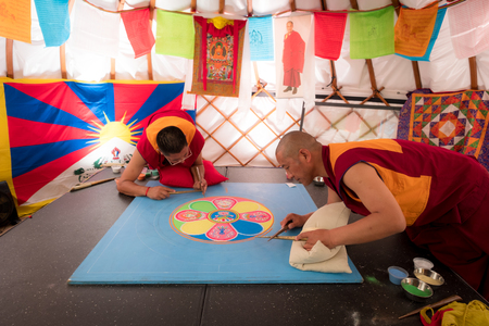 SYDNEY, AUSTRALIA - November 25, 2017: Buddhist monks making sand mandala, This is a Tibetan tradition of creation and destruction of mandalas made from colored sand